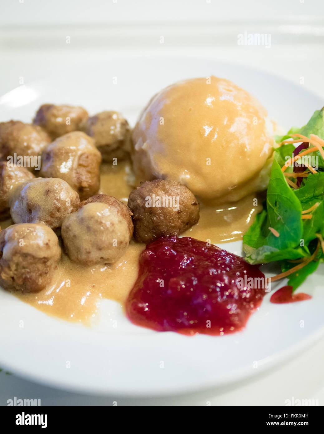 Eine Platte von IKEA Frikadellen, Kartoffelpüree, Sahne Soße, grüner Salat und Preiselbeer-Sauce. Stockbild
