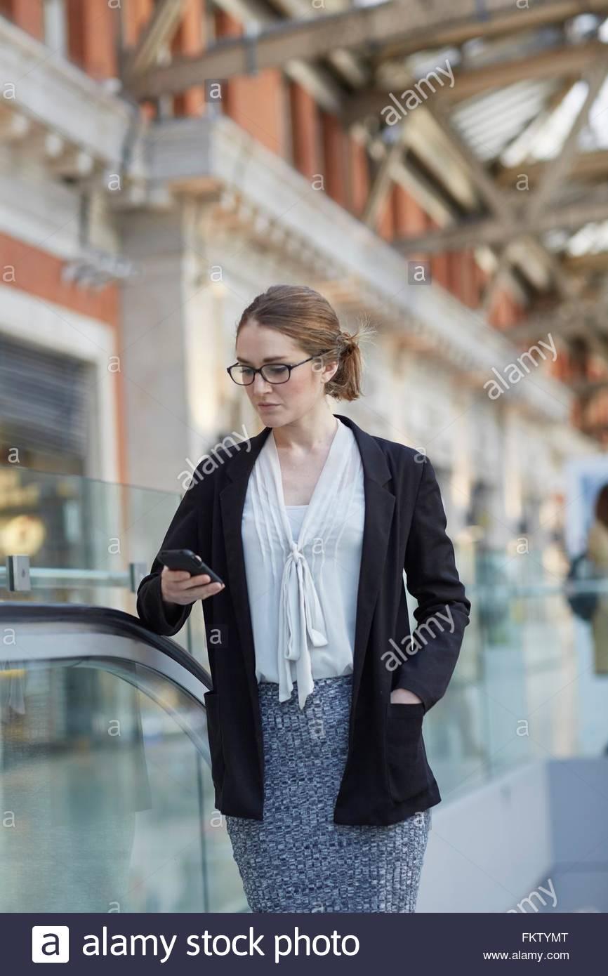Geschäftsfrau auf Rolltreppe nach unten smartphone Stockbild
