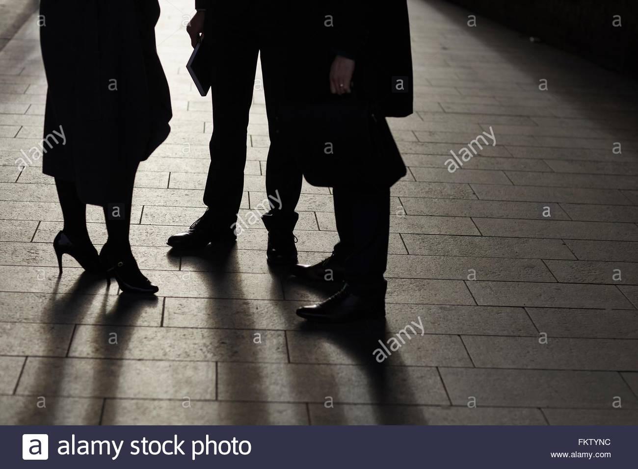 Taille abwärts von Geschäftspartnern stehen Pflaster von Angesicht zu Angesicht sprechen Stockbild