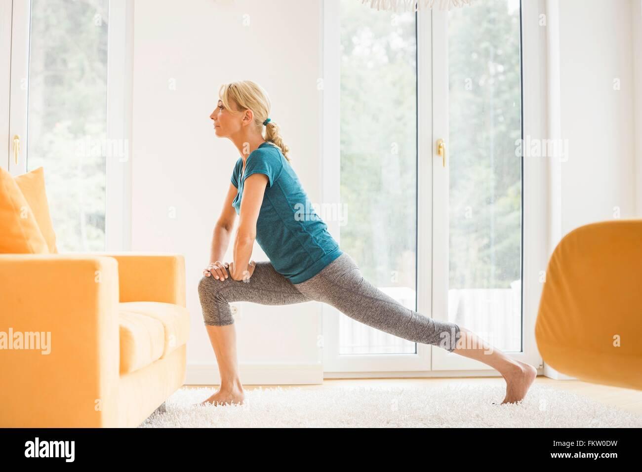 Reife Frau Longe Stretch trainieren im Wohnzimmer Stockfoto