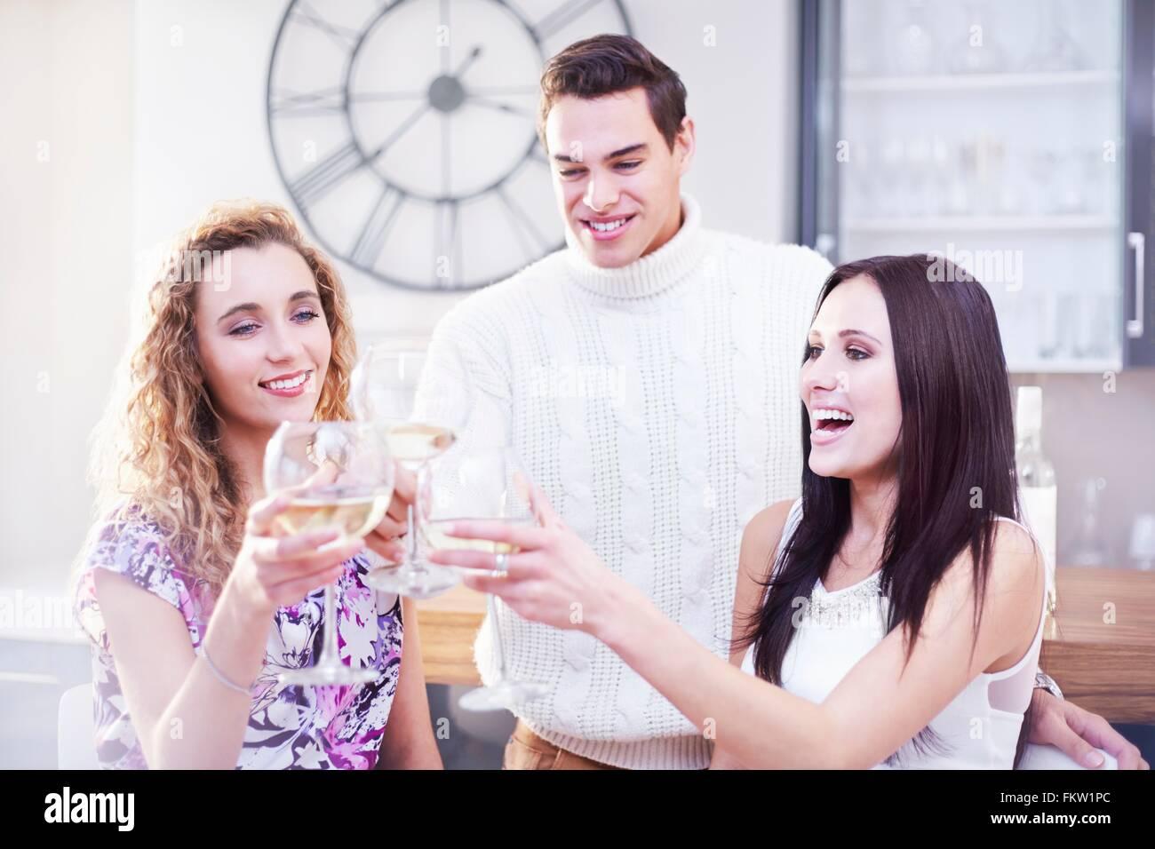Drei junge Erwachsene Freunde machen einen weißen Wein Toast in Küche Stockbild