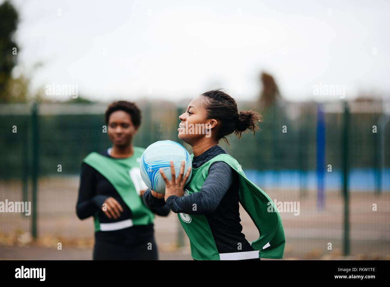 Junge Erwachsene weibliche Netball Spieler spielen Korbball Gericht Stockbild