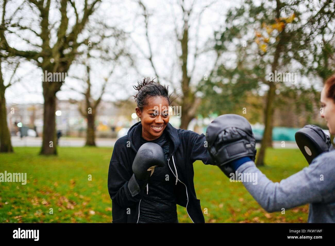 Junge Erwachsene Boxerinnen im Park zusammen zu trainieren Stockbild