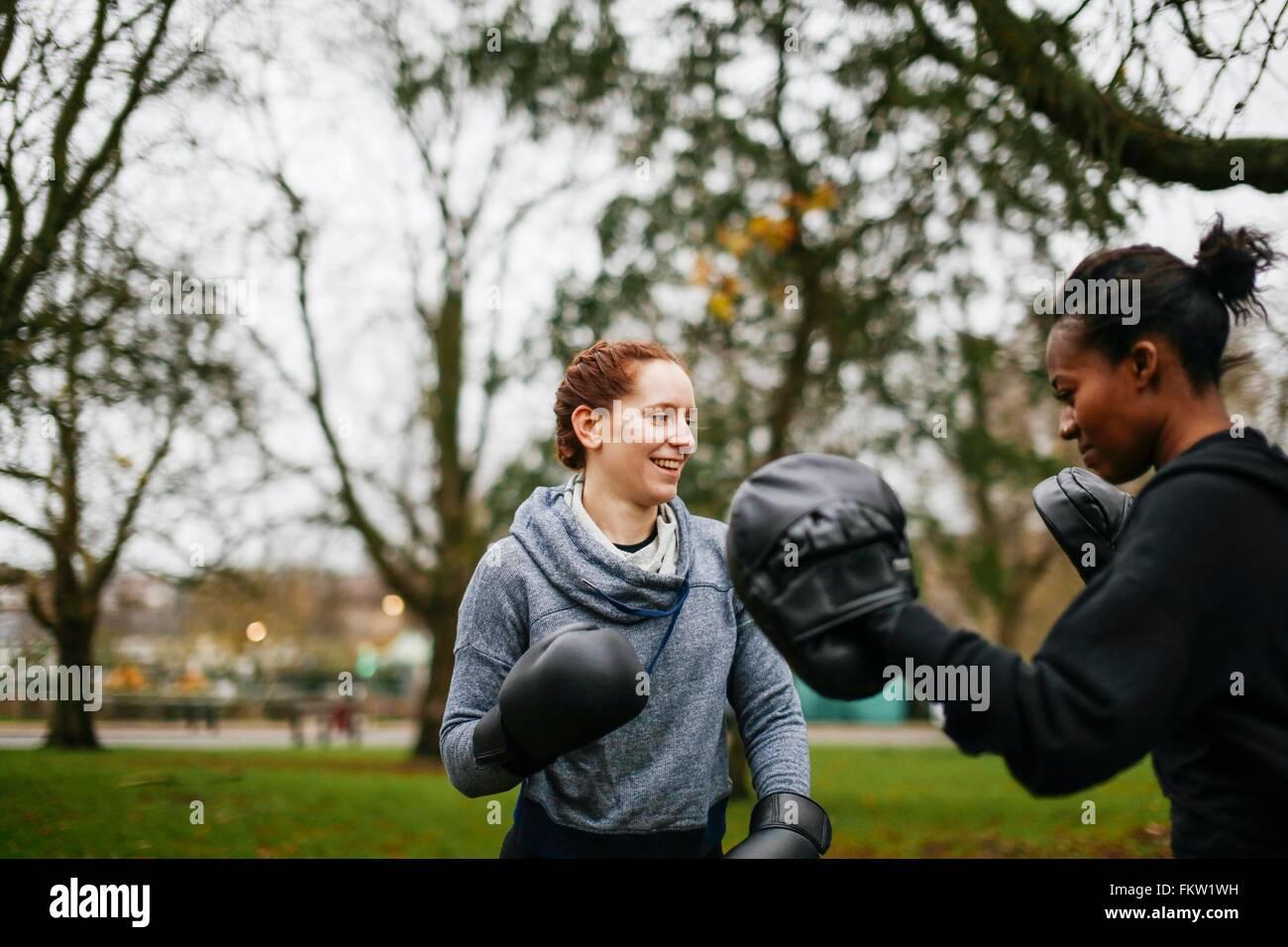 Junge Erwachsene Boxerinnen training im park Stockbild