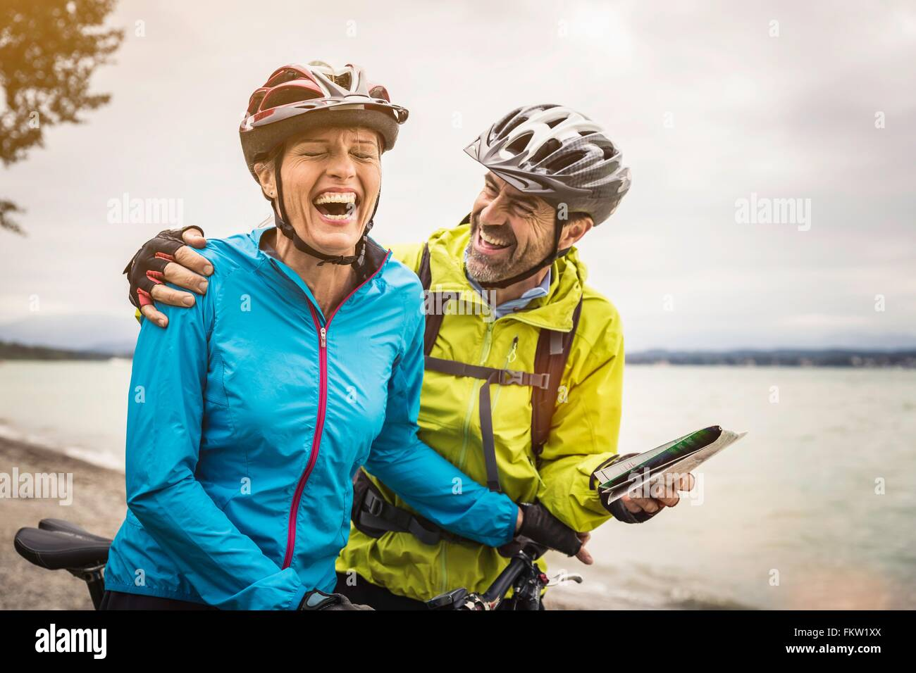 Reifen Sie Mountain Bike paar lachen während Check-Karte am Seeufer Stockbild