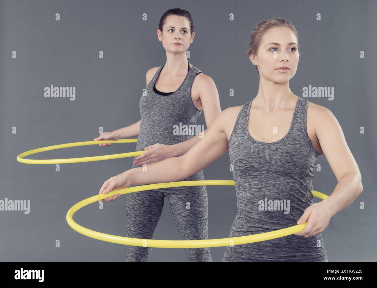 Junge Frauen, die sich darin üben, mit Hula-Hoop, grauer Hintergrund Stockbild