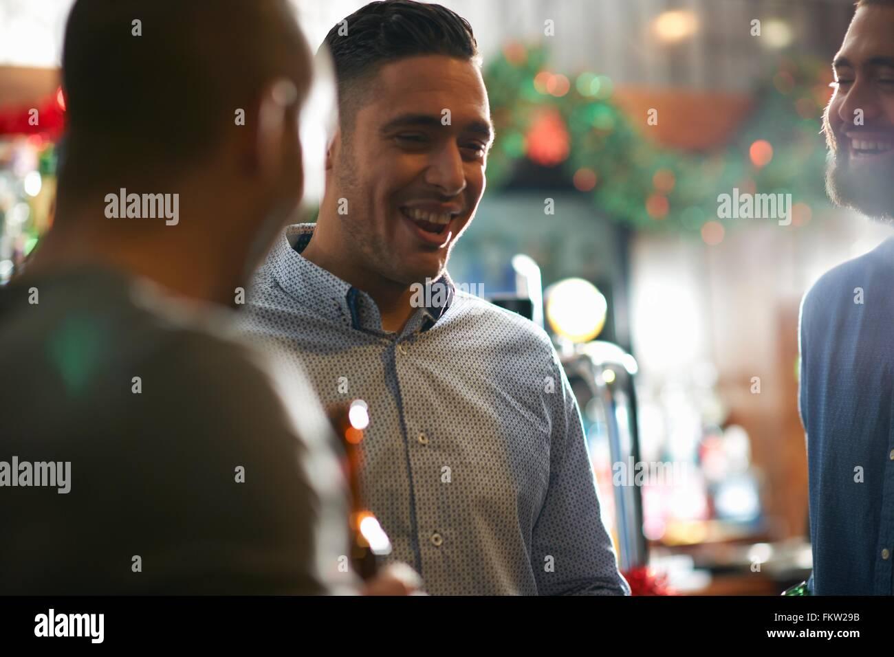 Junger Mann im Wirtshaus mit Freunden lächelnd Stockbild