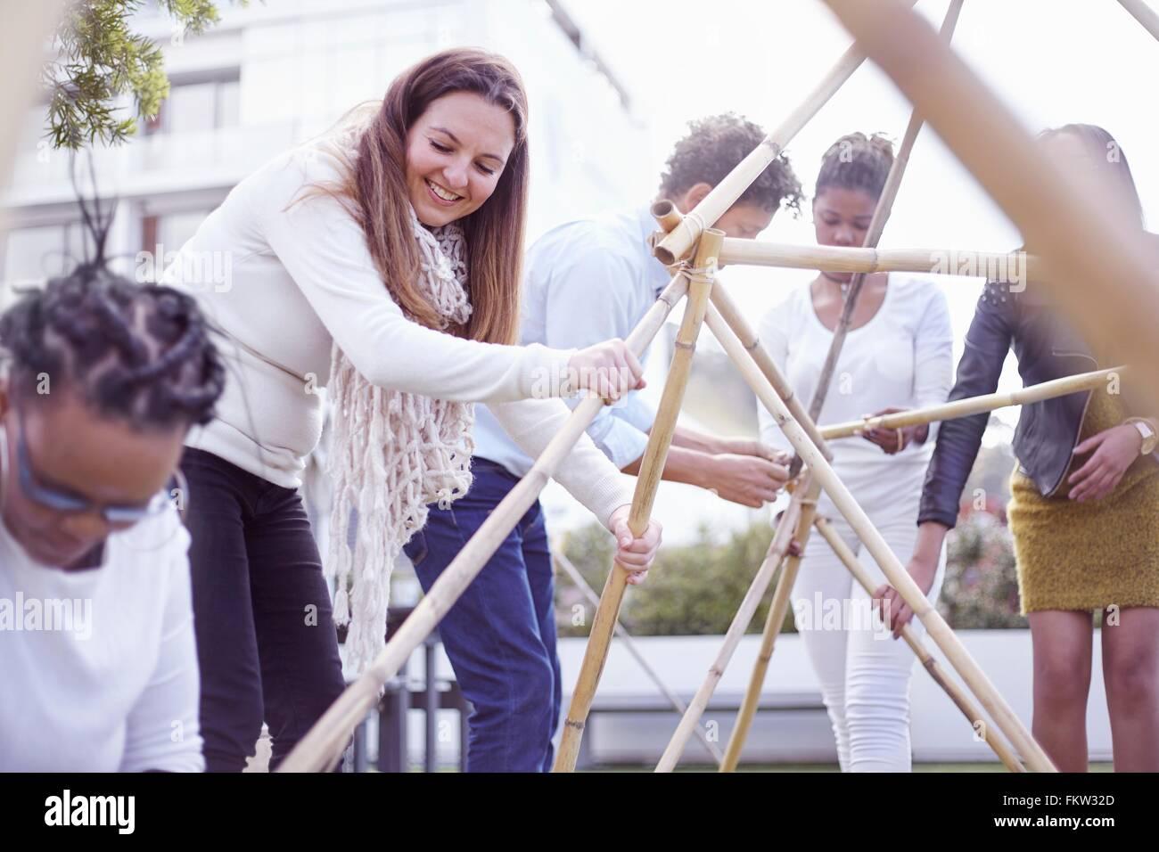 Kolleginnen und Kollegen im Team-building Aufgabe Gebäude hölzerne Struktur lächelnd Stockbild