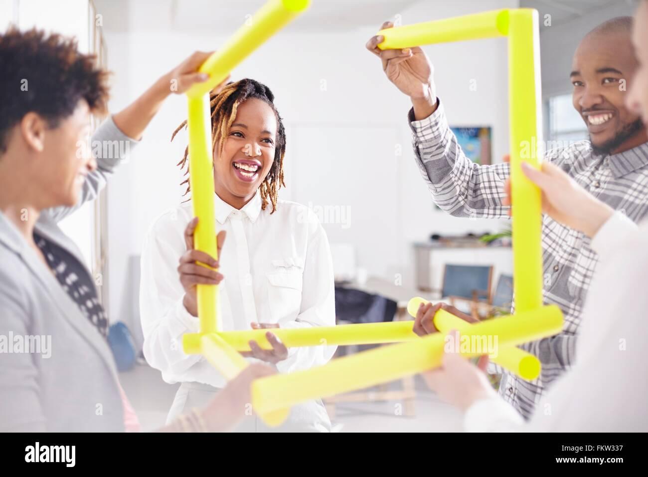Kolleginnen und Kollegen im Team-building Aufgabe hält gelbe Rubes lächelnd Stockbild