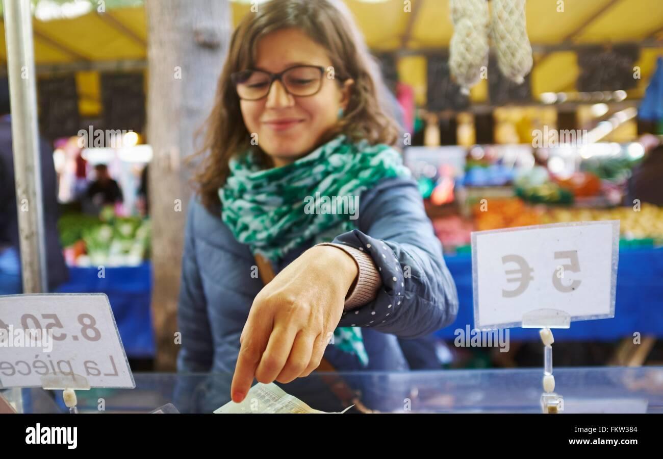Junge Frau waren am Marktstand kaufen Stockbild