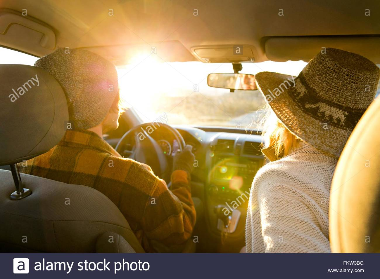 Rückansicht des jungen Paares in Auto, Sonnenlicht auf Windschutzscheibe Stockfoto
