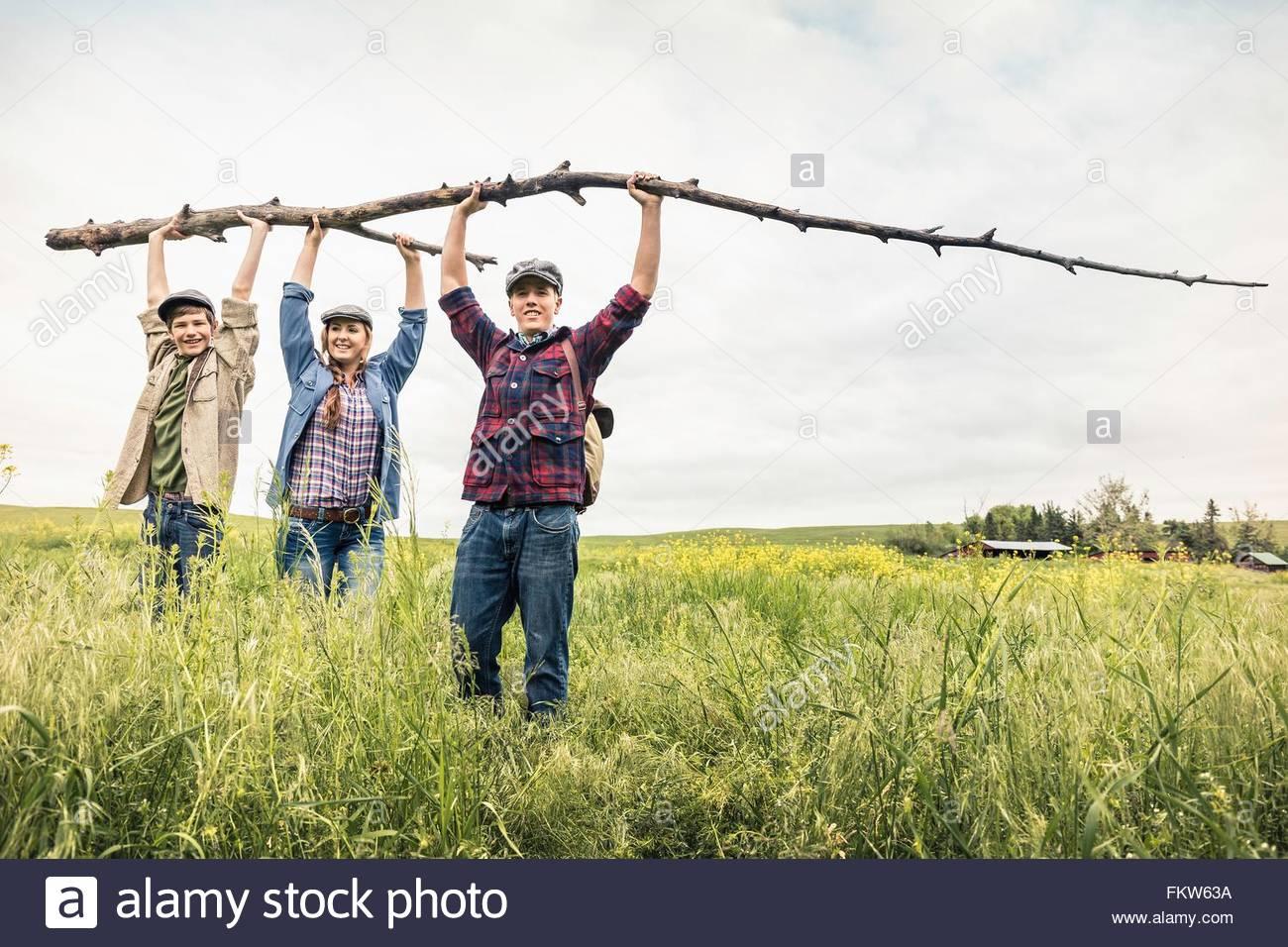 Junge Erwachsene und teenboy in hohe Gräser hält Zweig Blick auf die Kamera zu Lächeln Stockbild