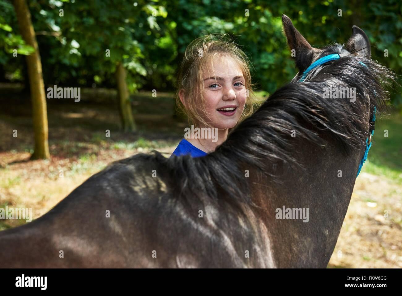 Kopf und Schultern des Mädchens mit Blick auf die Kamera zu Lächeln Pferd Stockbild