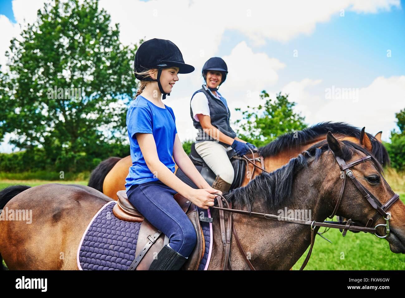 Seitenansicht der Reife Frau und Mädchen auf Pferde tragen Reiten Hüte lächelnd Stockbild