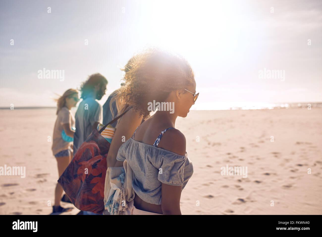 Aufnahme einer Gruppe von jungen Freunden an einem sonnigen Tag am Strand entlang spazieren. Männer und Frauen, die Sommer-Urlaub am Strand. Stockfoto