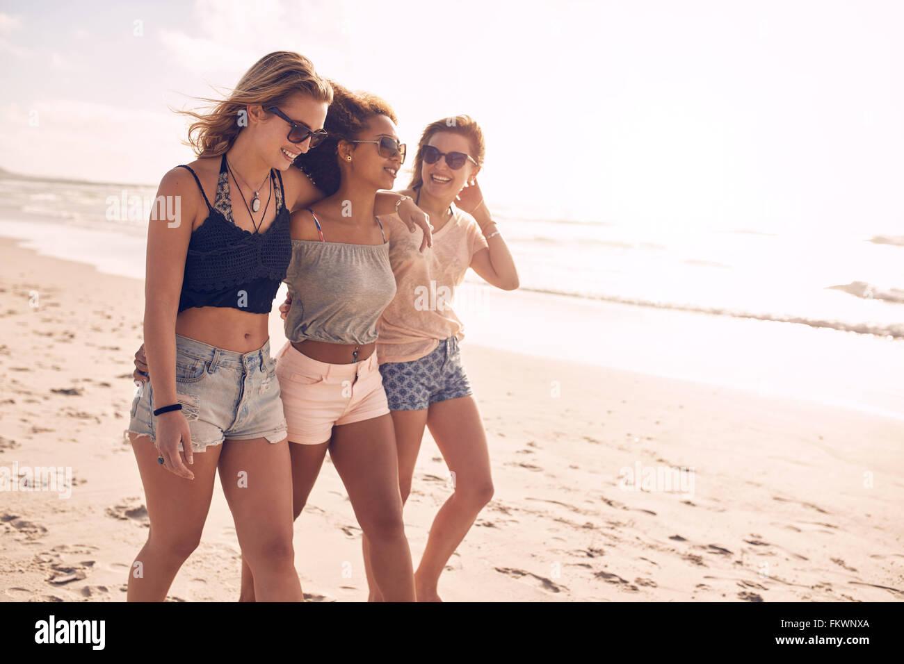 Porträt von drei jungen Freundinnen zu Fuß am Ufer Meeres. Gemischtrassig junge Frauen, die an einem Sommertag Stockbild