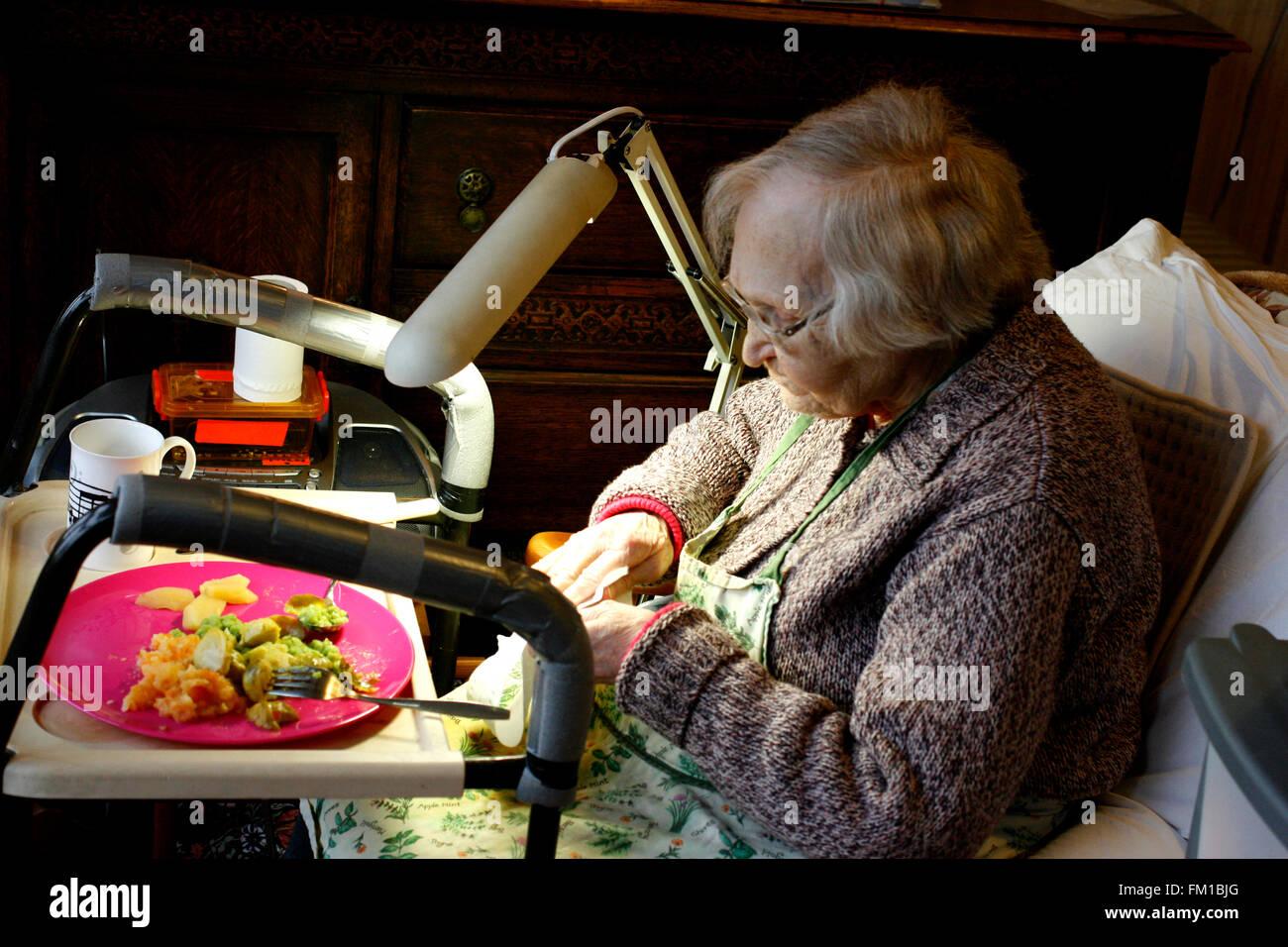 Senioren-Dame zu Hause sitzen mit ihr Abendmahl London uk März 2016 Stockbild