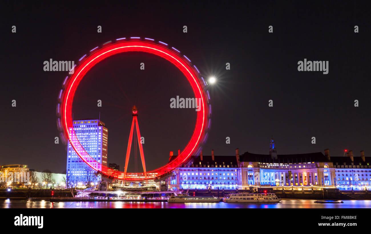 London bei Nacht - beleuchtete London Eye Riesenrad und Stadt Skyline bei Nacht, Vollmond scheint hinter Stockbild