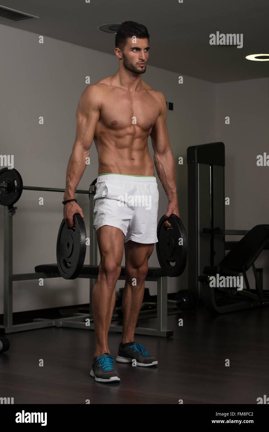 Portrait eines jungen Fit körperlich Mann hält Gewichte