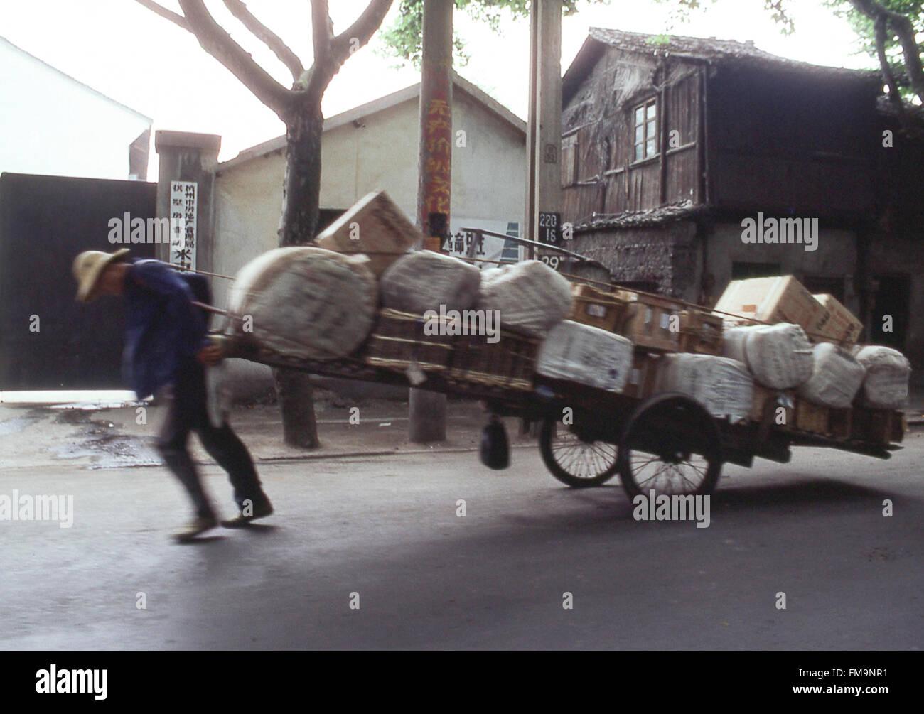 Chinesischer Mann zieht schwer beladenen Wagen entlang der Straße in China in den 1980er Jahren Stockbild
