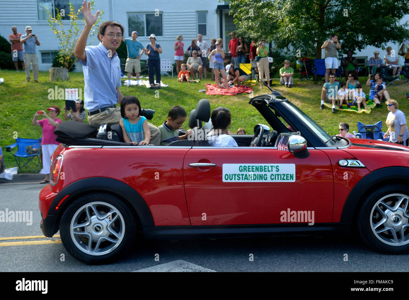 Herausragende Ctizen Greenbelt Fahrten in der Tag der Arbeit mit seinen Kindern in einer Parade in Greenbelt, Maryland Stockbild
