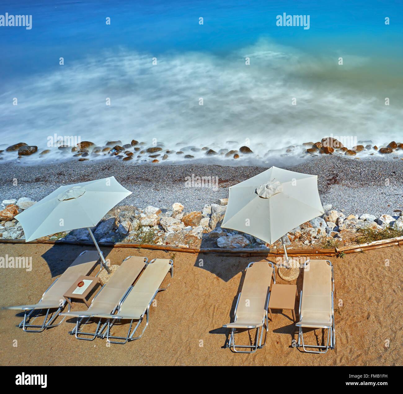 Küstenlandschaft mit Sandstrand, Sonnenliegen und Sonnenschirmen. Stockbild