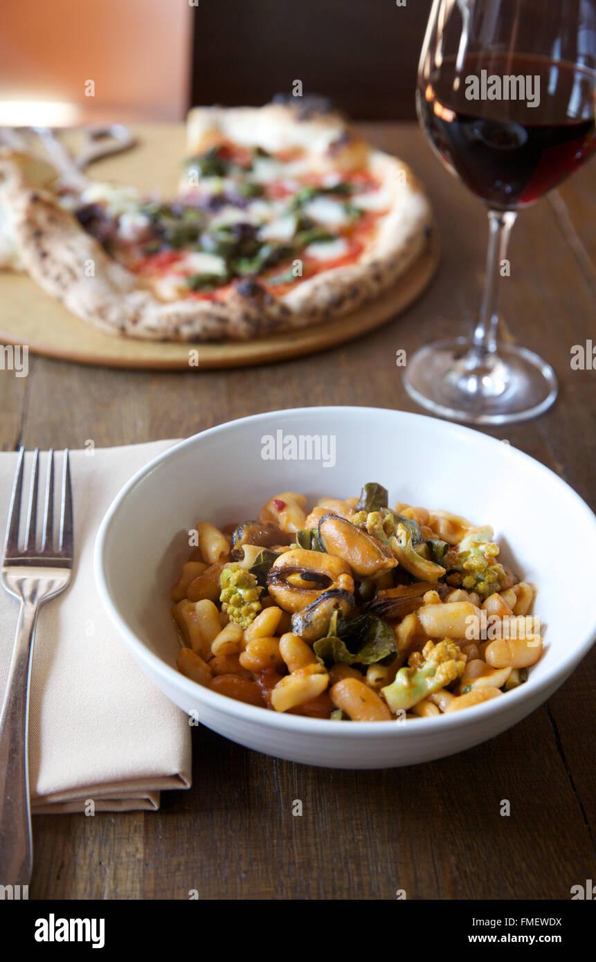 Eine Schale mit weißen Bohnen, Romanesco und Muscheln Suppe mit Rotwein und eine Pizza auf dem Tisch hinter Stockbild
