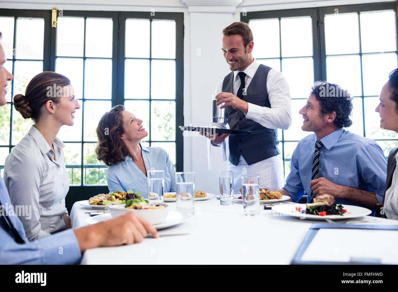 Kellner servieren Wasser für Geschäftsleute Stockbild