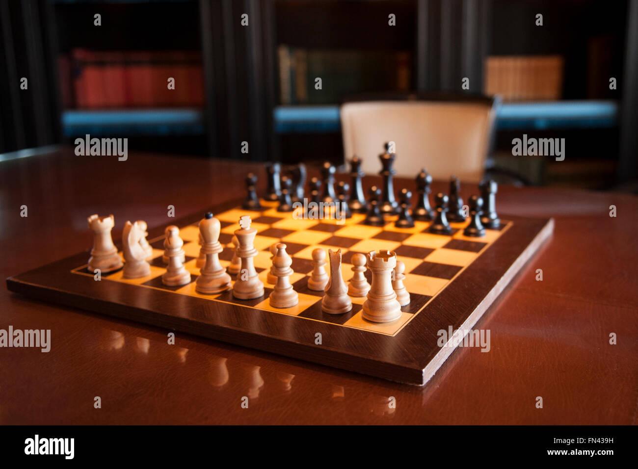 Schachbrett mit Stücken reflektiert auf Tisch in Bibliothek und Studie Stockfoto