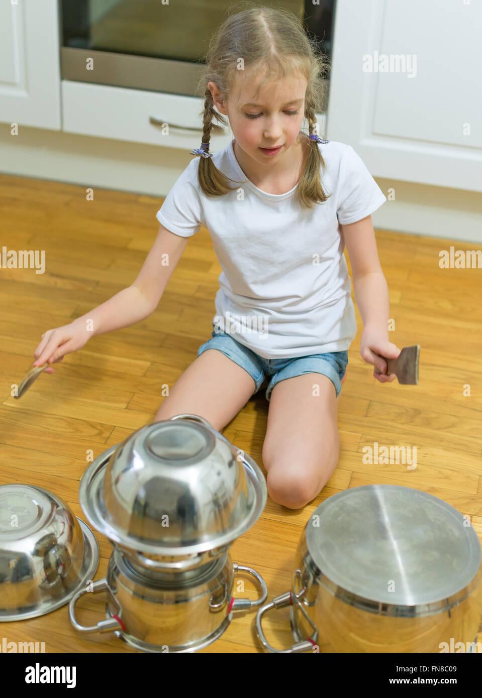 Kleine Mädchen spielen Trommeln auf Töpfe und Pfannen in der Küche ...