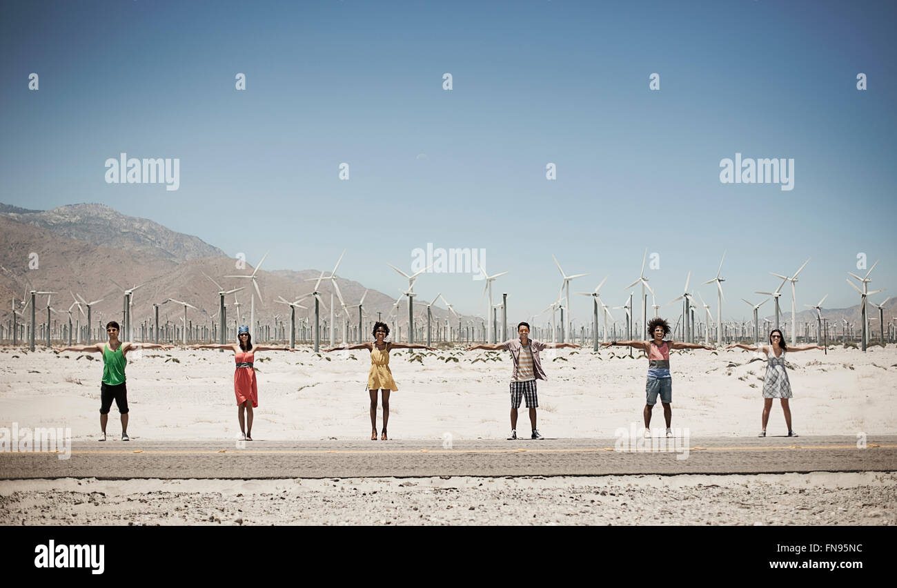 Eine Reihe von sechs Jugendlichen stehen ausgestreckten am Straßenrand mit einem Hintergrund von Windkraftanlagen. Stockbild