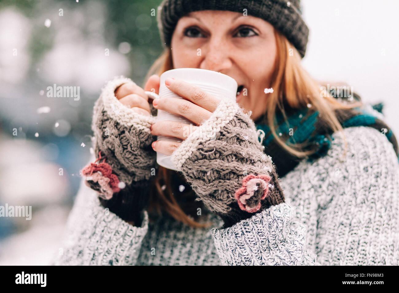 Frau im Schnee hält heißes Getränk Stockbild