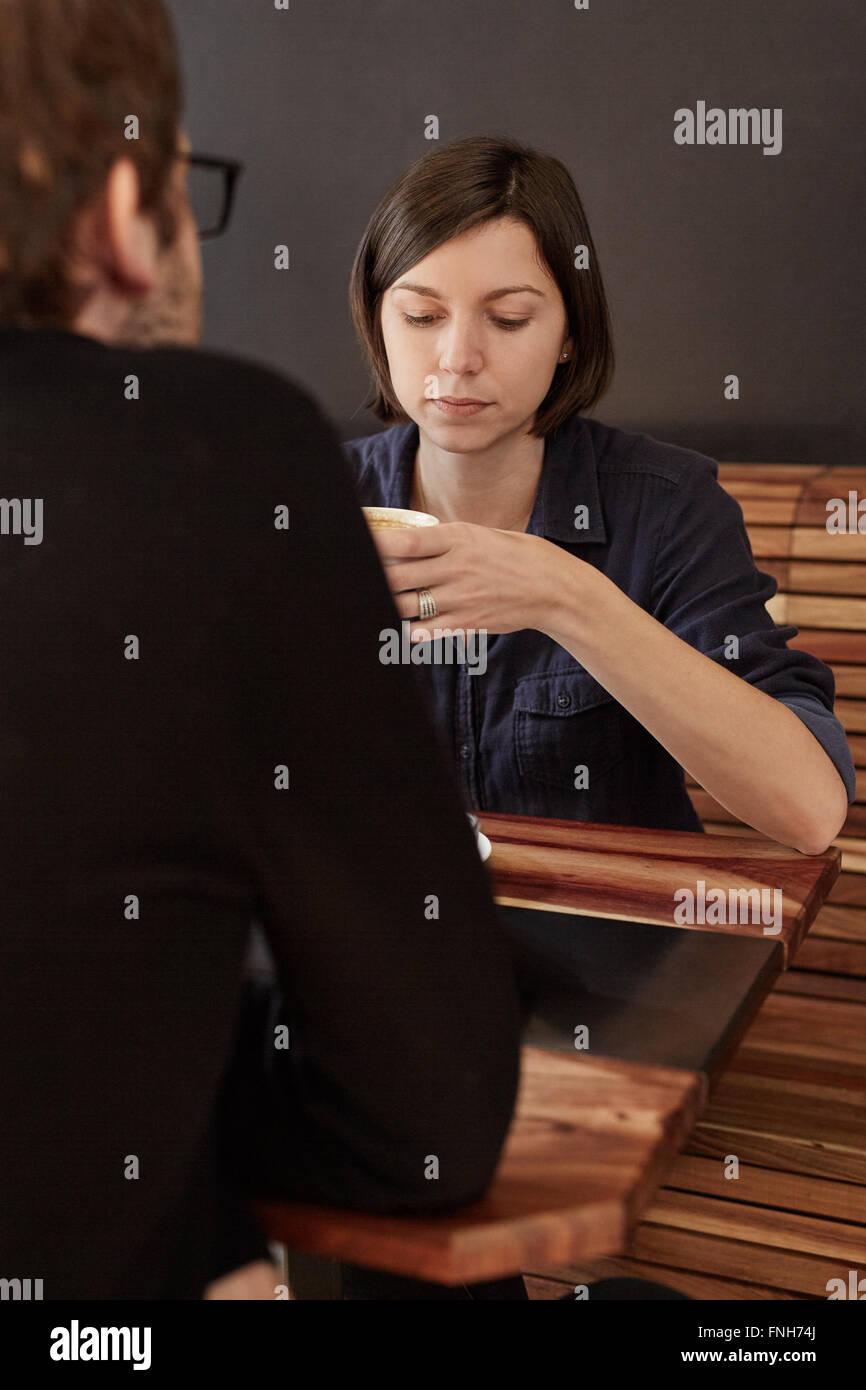 Frau sucht ernsthafte beim Kaffeetrinken mit Freund in Kalifornien Stockfoto