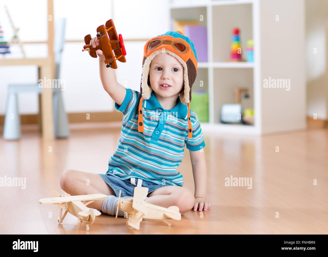 Glückliches Kind spielen mit Spielzeugflugzeug zu Hause Stockbild