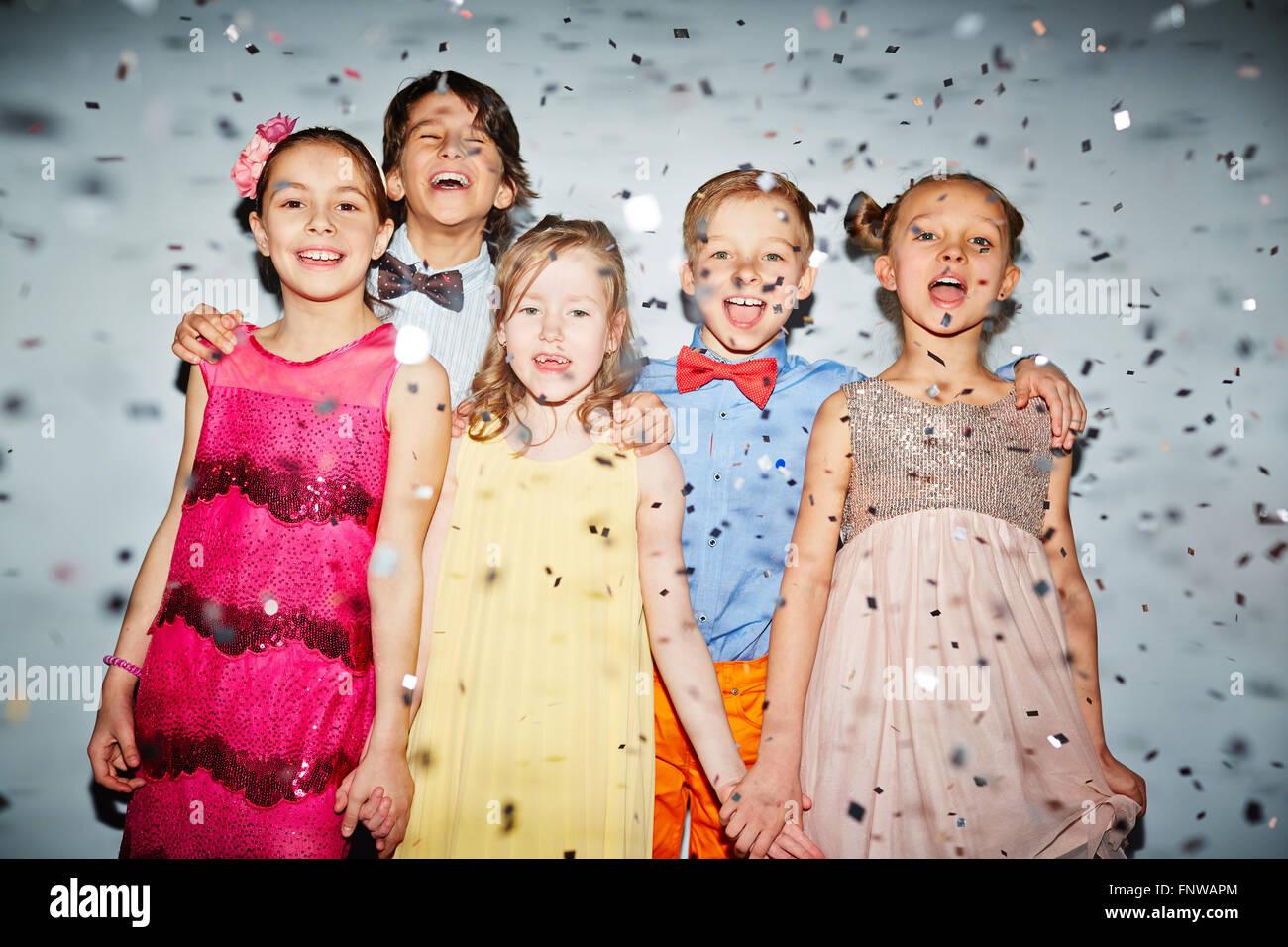 Gruppe von glücklichen Kindern stehen unter fallenden Konfetti Stockbild