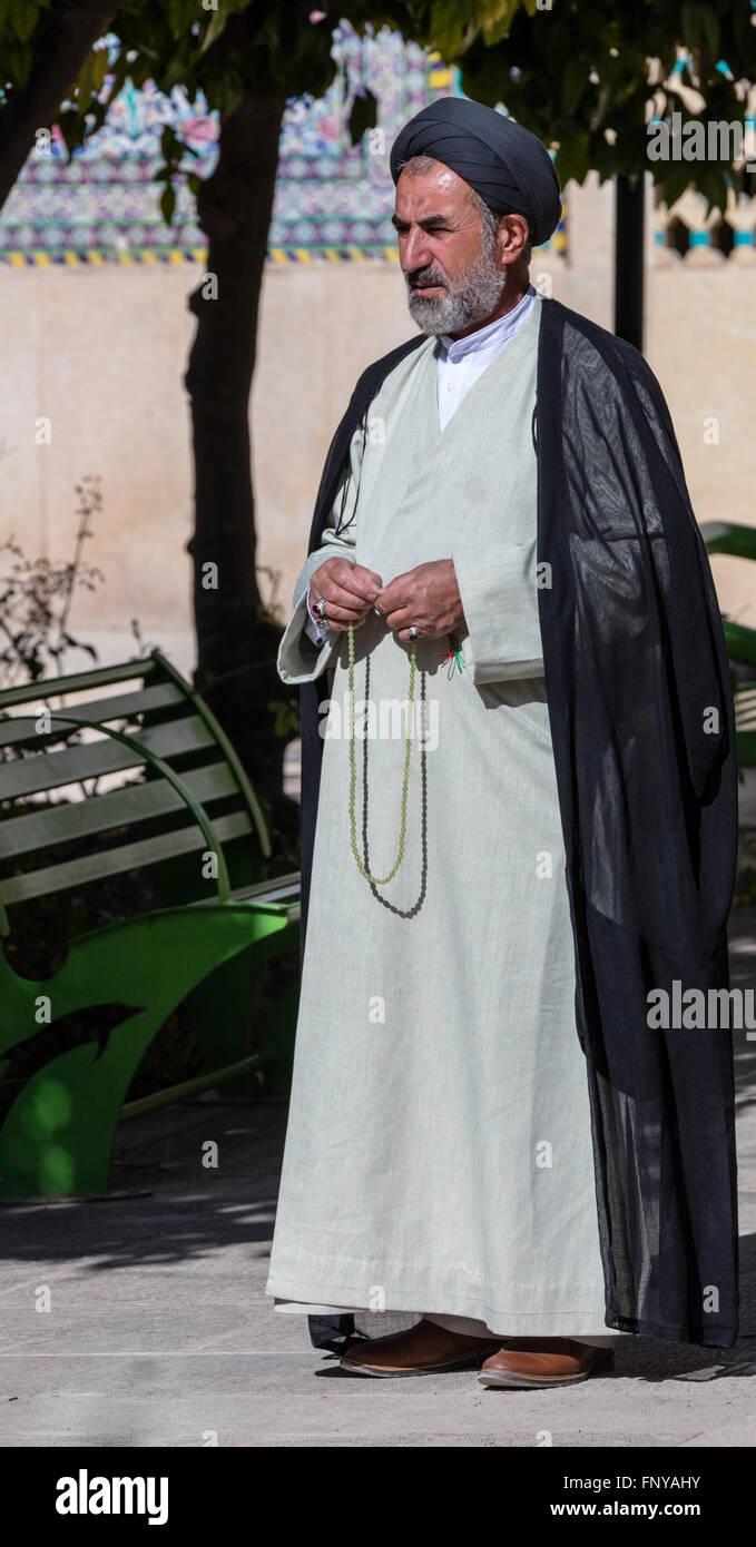 Mullah im Turban und Gewand mit Komboloi steht im Hof des Khan Medrassah, Shiraz, Iran Stockbild