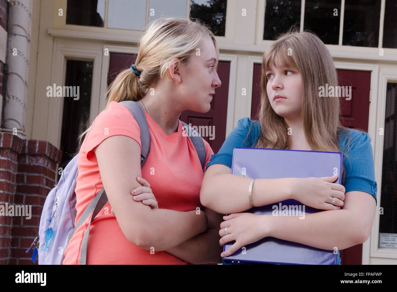Eine aggressive Teengirl schüchtert ein anderes Mädchen vor ihrer Schule, wahrscheinlich über einen Stockbild