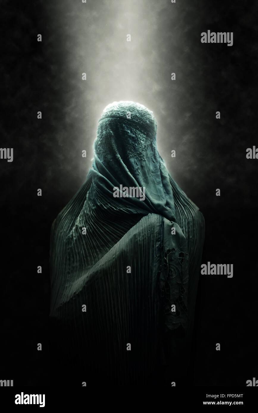 Verschleierte islamische Frau trägt eine Burka steht in einem Strahl von Licht in atmosphärischen Dunkelheit Stockbild