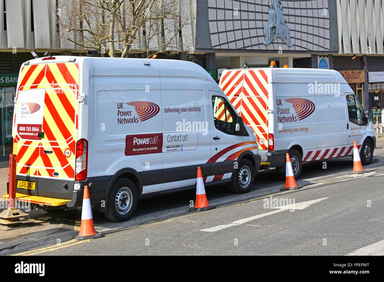 Zwei UK Power Networks vans geparkt während Straße arbeiten an unterirdischen Stromlieferungen wird in Stockbild