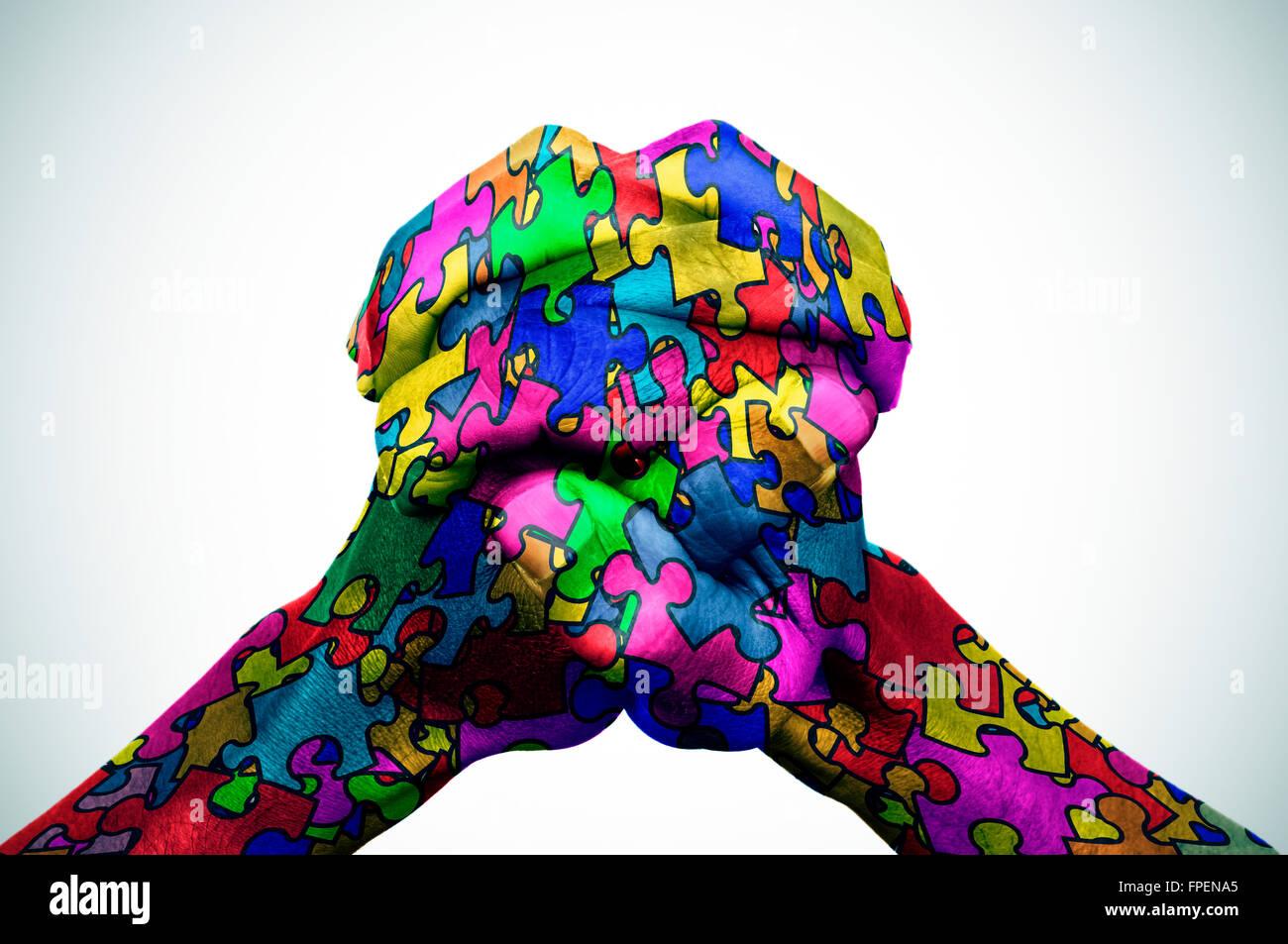 Hände des Mannes zusammen mit viele Puzzle-Teile in verschiedenen Farben, Symbol des Autismus, mit einem leichten Stockfoto
