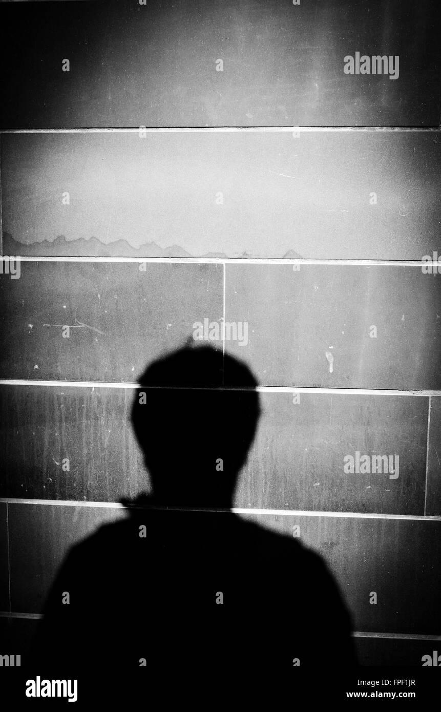 Silhouette einer Person an einer Wand. Stockbild