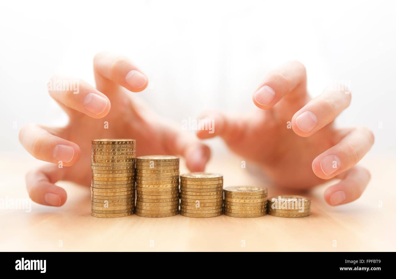 Gier nach Geld. Hände greifen Münzen. Stockbild