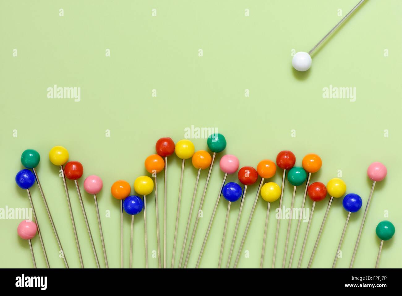 Bunte Beeren Pins auf grünem Hintergrund mit weißen Kuckucksei von selbst mit Konzept der Kuckucksei heraus Stockbild