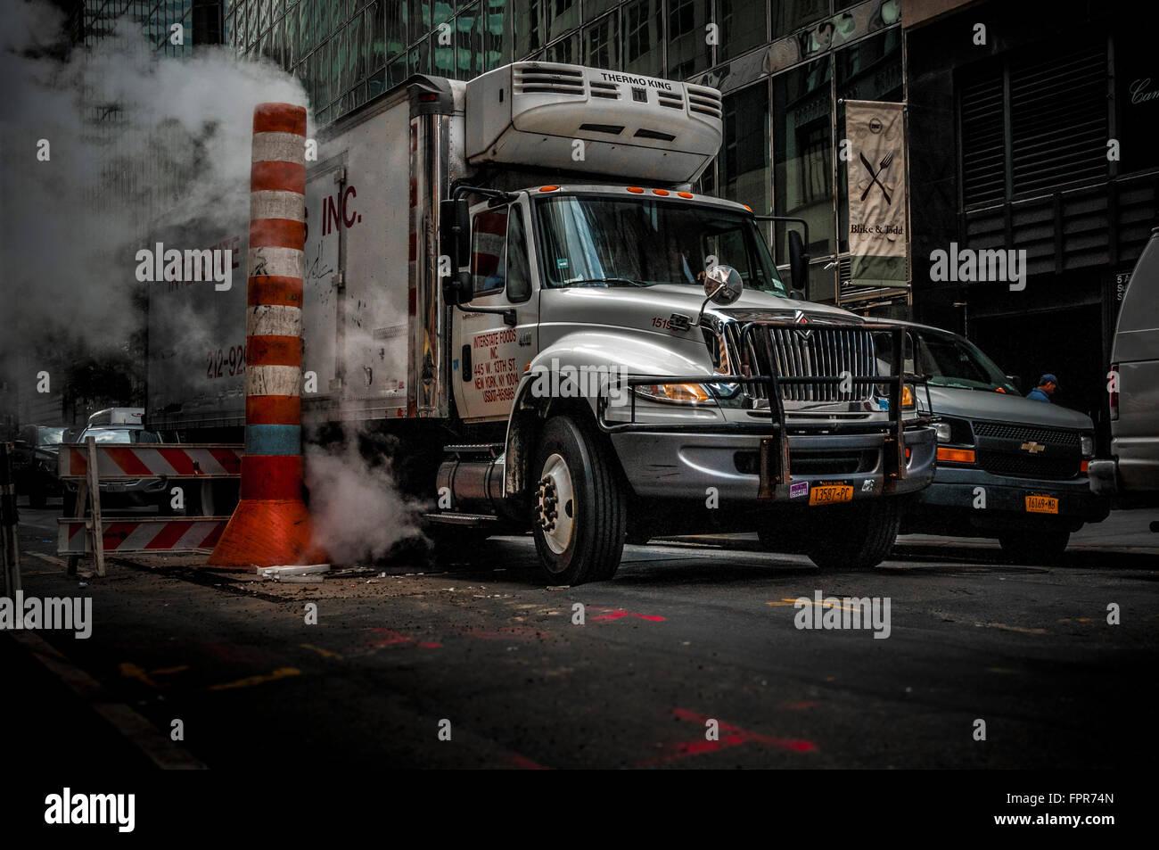 LKW und Dampf Dampf wird durch eine typische Con Edison Orange und weiße gelüftet stapeln, New York City, Stockbild
