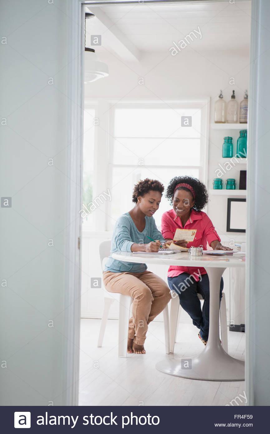 Mutter und Erwachsene Tochter Rezepte zusammen betrachten Stockbild