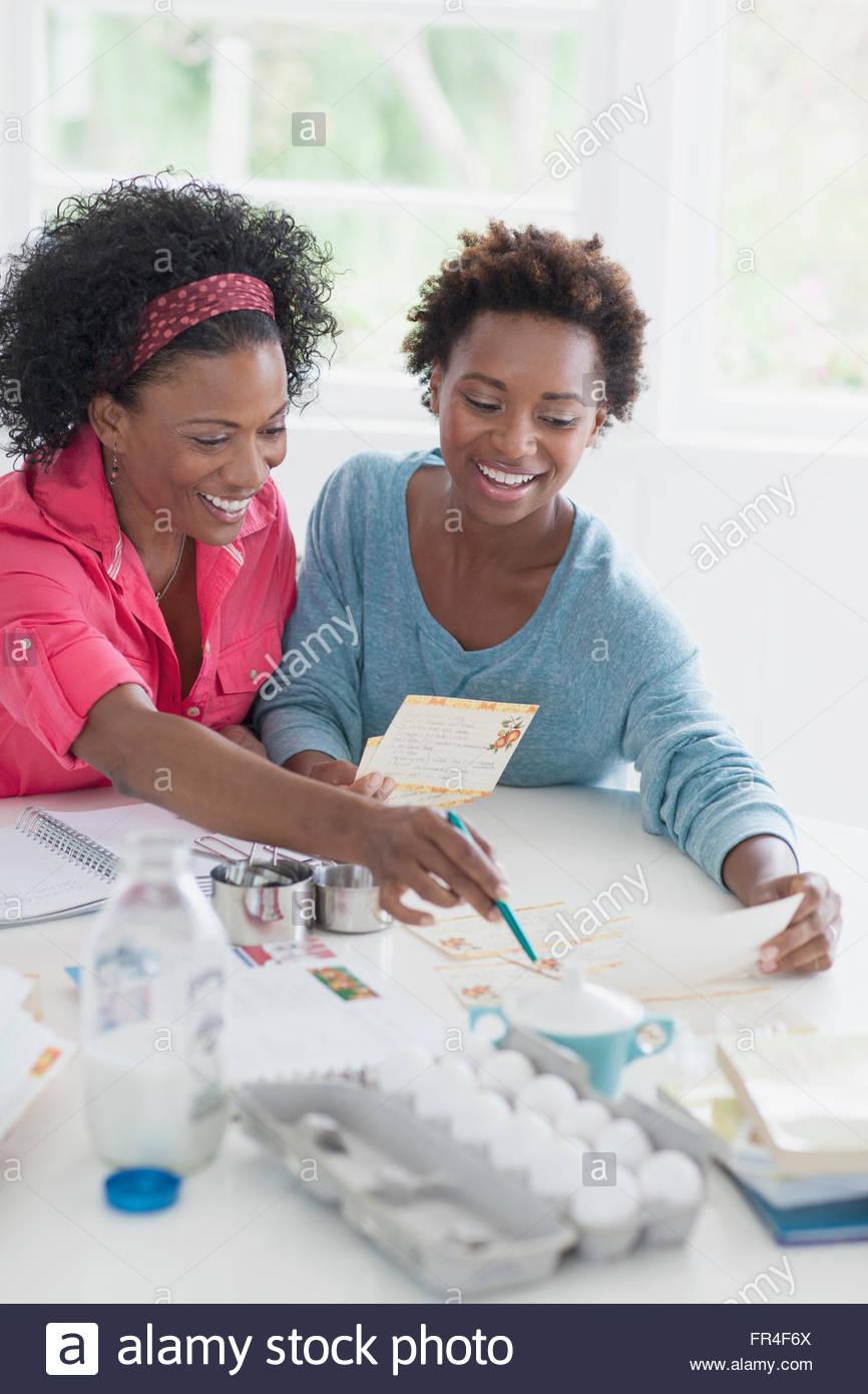Mutter und Erwachsene Tochter Durchsicht Rezepte Stockbild