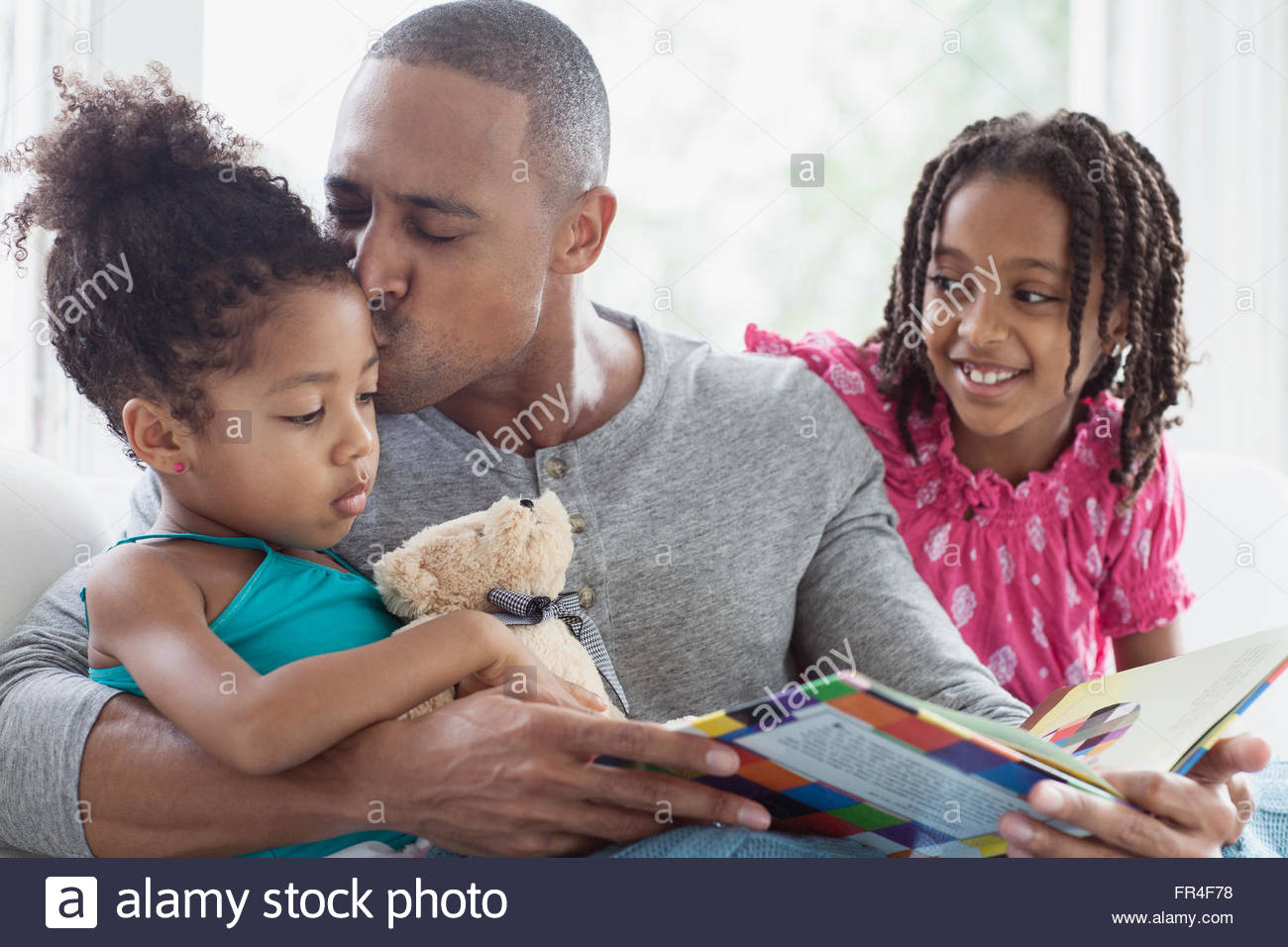 Papa, die jüngste Tochter während Storytime küssen Stockbild