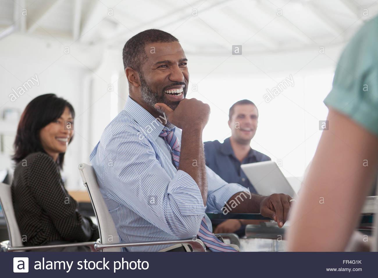 attraktive Mitte Alter Geschäftsmann mit einem Lachen während eines Meetings Stockbild