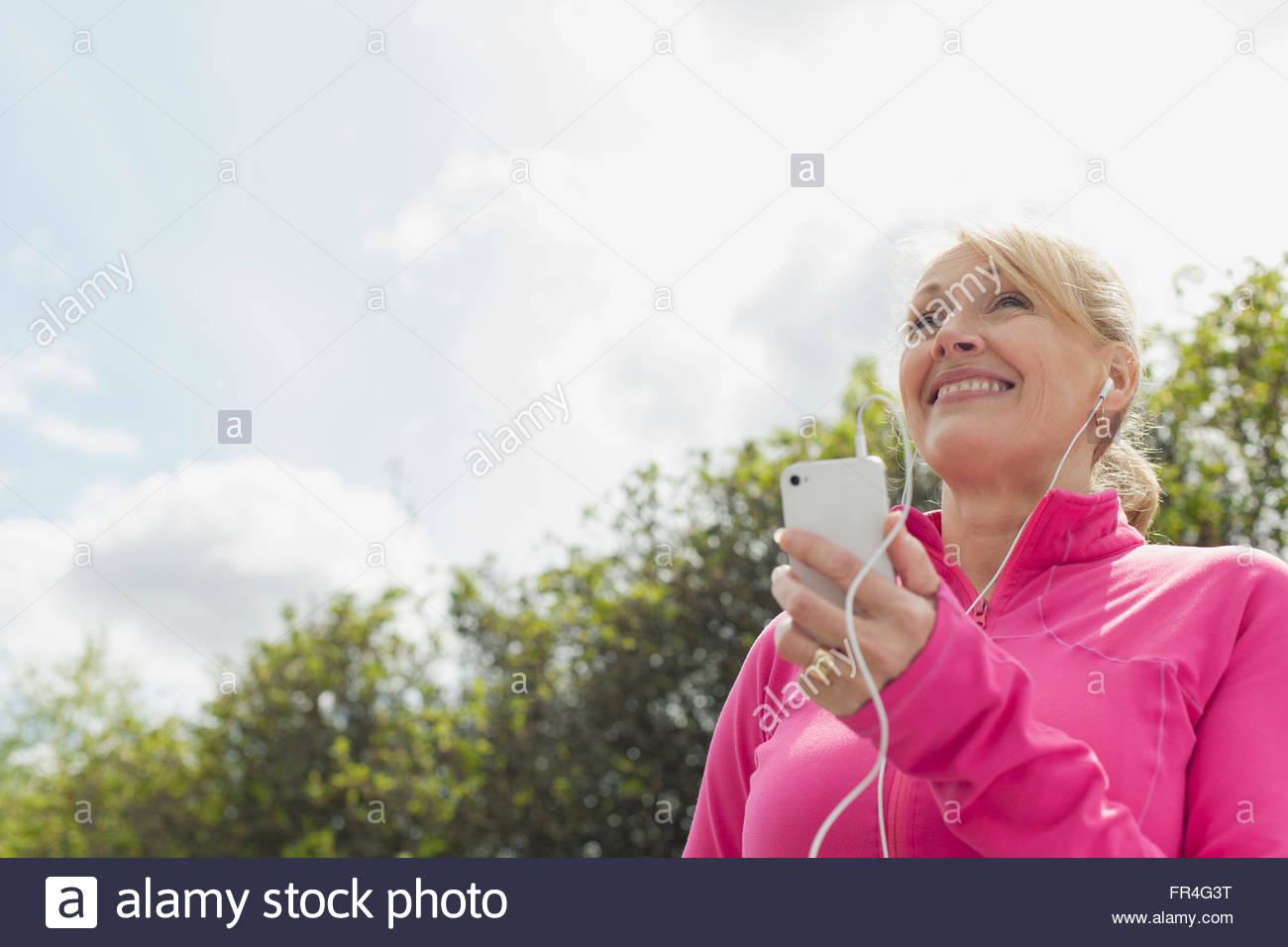 Ältere Frau anhören von Musik auf Smartphone in der Stockbild