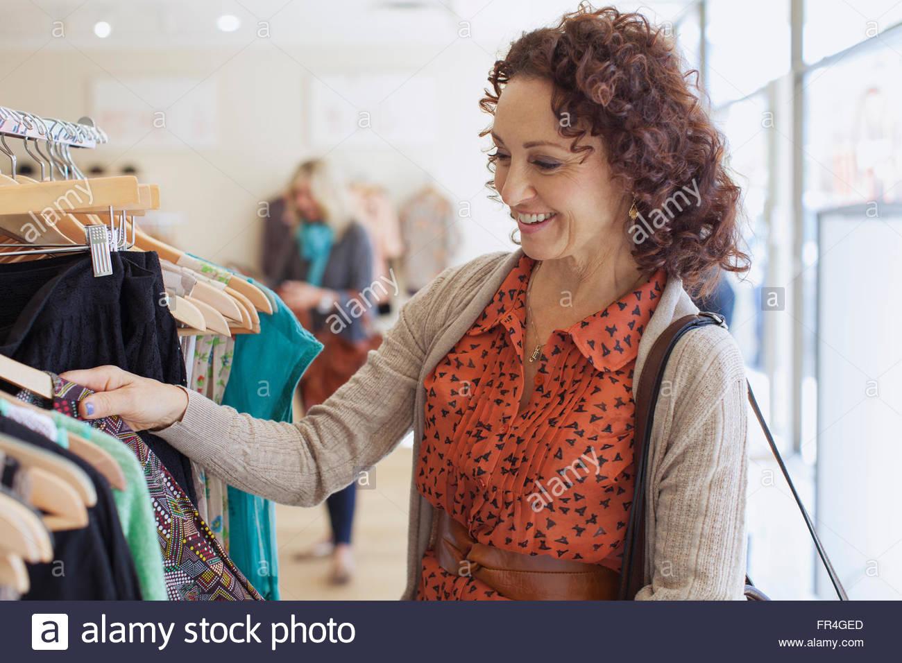 Frau Racks von Kleidung im trendigen Store durchsuchen. Stockbild